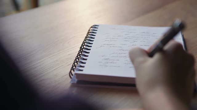 close-up-of-a-woman-writer-hand-writing-in-a-notebook-at-home-in-the-kitchen-raw-video-record_exf5hnj49e__m0000